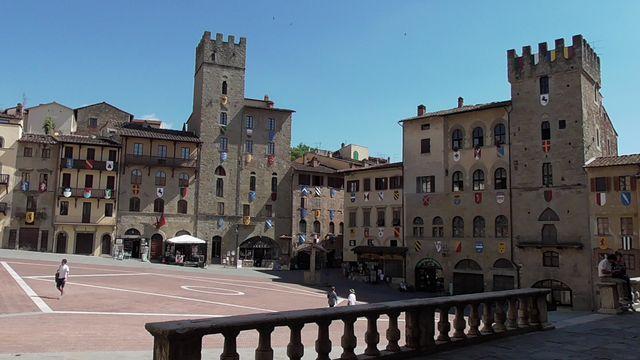 Po prawej Torre Faggiolana po lewej w głębi Palazzo Lappoli, złozony z budynków o różnej wysokości z drewnianymi balkonami.